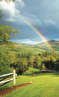 A rainbow hangs over a green field of the White Mountains